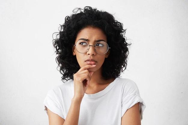 Mulher de óculos com expressão de dúvida em fundo branco