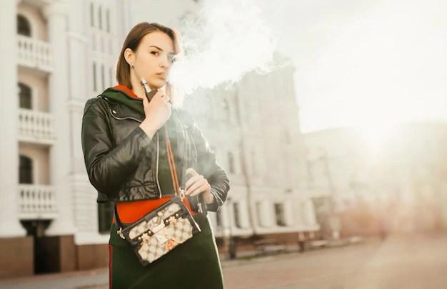 美しい若い女性は煙を吸う。若い女の子は都市の背景に向かっている。 | 無料の寫真