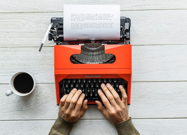 Aerial view of a man typing on a retro typewriter Free Photo