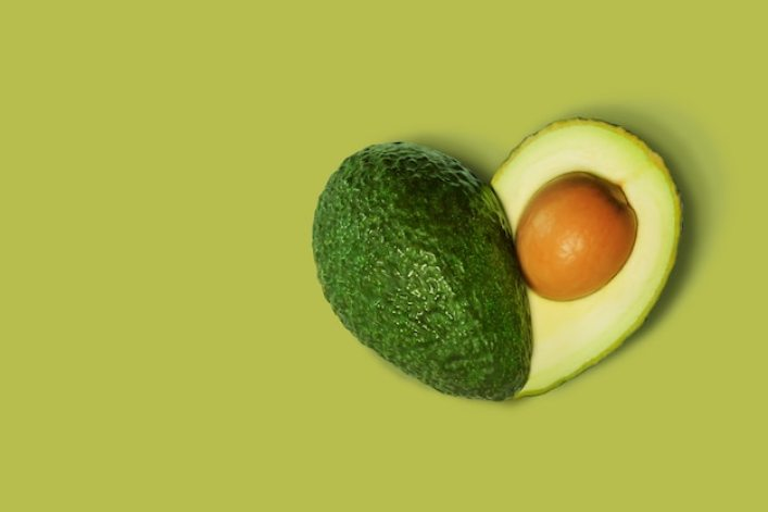 Avocado Isolated on Green in shape of Heart Premium Photo