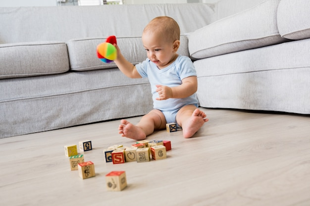 Baby boy sitting on floor and playing with toys in living
