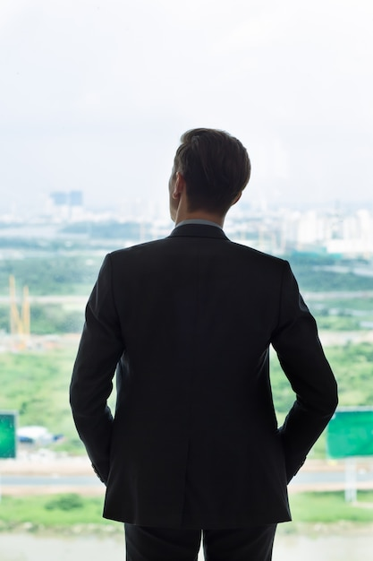 Back View of Businessman Looking at City in Window Photo