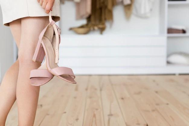 Vista de mulher segurando sapatos de salto alto pela mão.