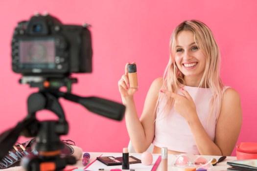 γυναίκα μπλόγκερ κοιτά σε κάμερα και δείχνει προιόν
