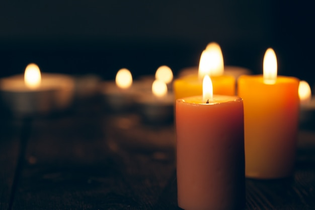 Candles burning in darkness over black background Premium Photo