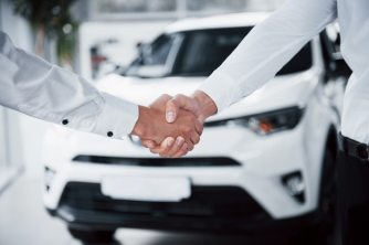 Close up of sales manager in black suit selling the car to the customer Free Photo