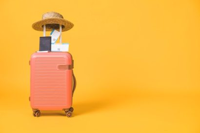 Composition of suitcase and tickets passport and hat on it Free Photo