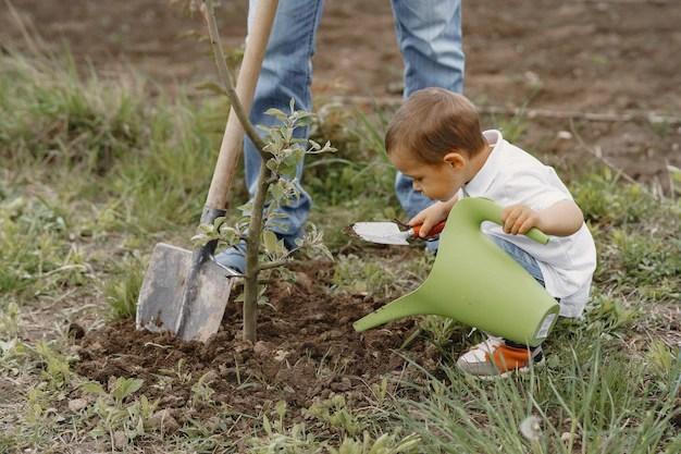 Anak kecil sedng meneliti pokok sambil siram pokok