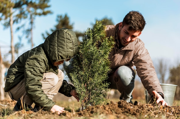 Father and son planting a tree Free Photo