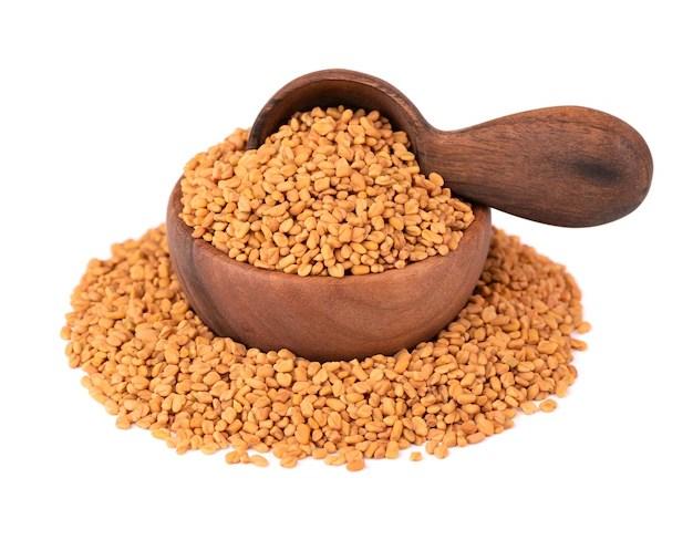 Fenugreek seeds in wooden bowl and spoon, isolated  shambala, helba seeds. Premium Photo