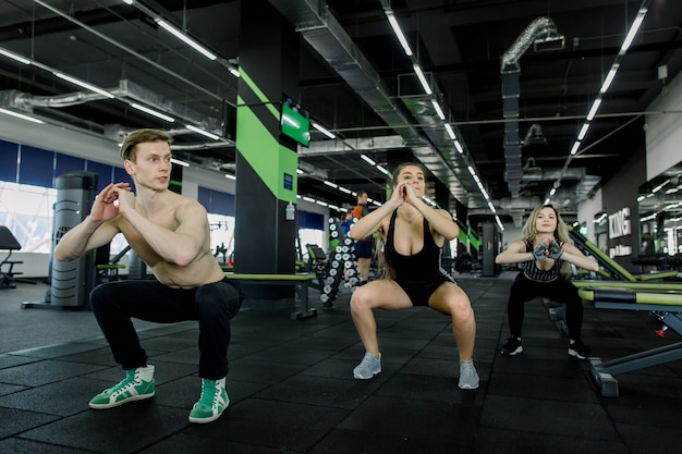 Premium Photo Fitness Sport Training Gym And Lifestyle Concept Group Of Smiling People Exercising In The Gym Doing Squats