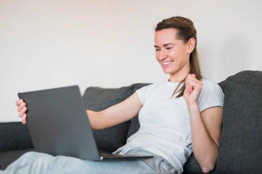 Γυναίκα κειμενογράφος βλέπει το λαπτοπ και χαμογελά