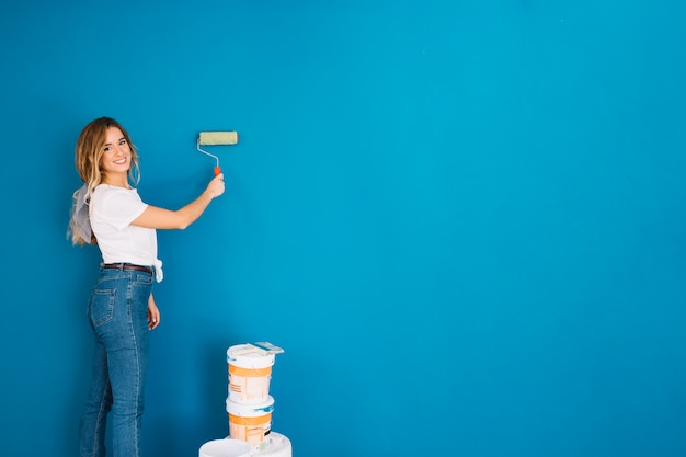 Girl painting wall with roll Photo