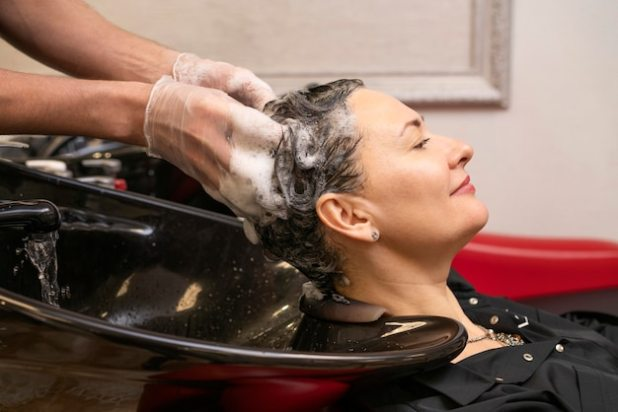 Hairdresser washing a woman's hair Free Photo