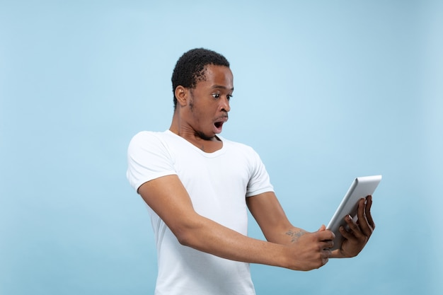 Half-length close up portrait of young african-american man in white shirt on blue wall. human emotions, facial expression, ad, sales, concept. using tablet, shocked, astonished. Free Photo
