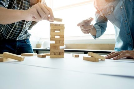 Hand of engineer playing a blocks wood tower game (jenga) on blueprint or architectural project Free Photo
