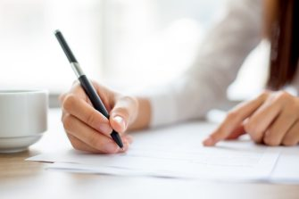 Hand of businesswoman writing on paper in office Free Photo