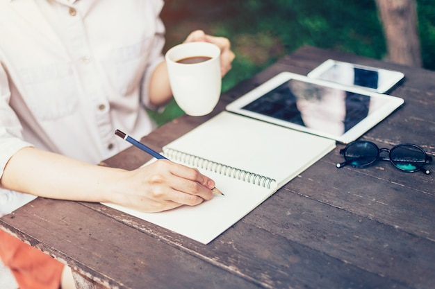 Hand woman writing notebook and holding cup coffee on wood table ...