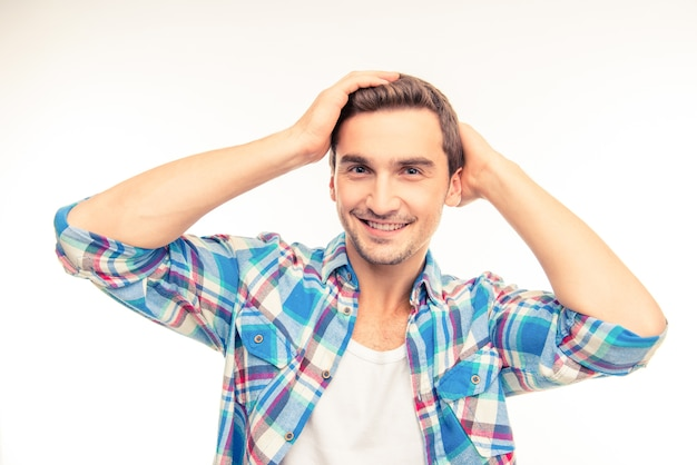 Handsome young man holding hands on his hair Premium Photo