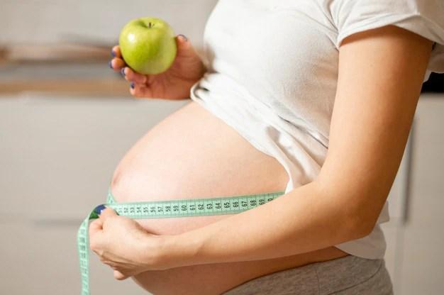 Vista lateral de uma mulher segurando uma maçã e medindo a barriga