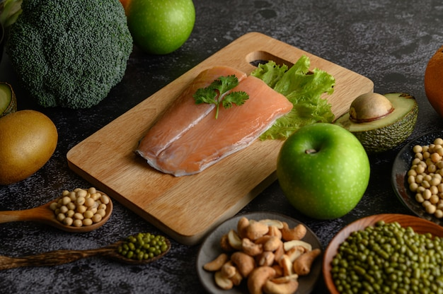 Legumes, fruit, and salmon fish pieces on a wooden chopping board. Free Photo