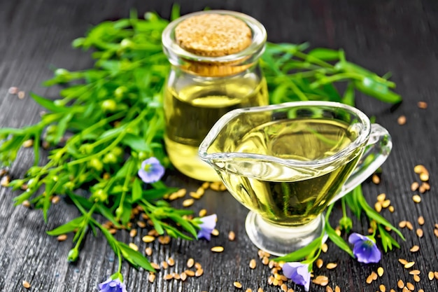 Linseed oil in a glass jar and gravy boat with seeds, leaves and flax flowers on a wooden board background Premium Photo