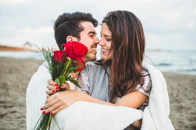 Loving couple sitting on a beach with a bouquet of roses Premium Photo