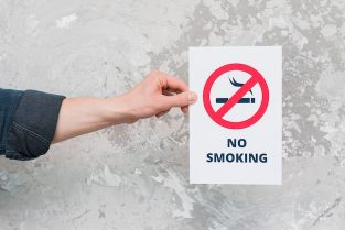 Male hand holding paper with no smoking sign and text over weathered wall Free Photo