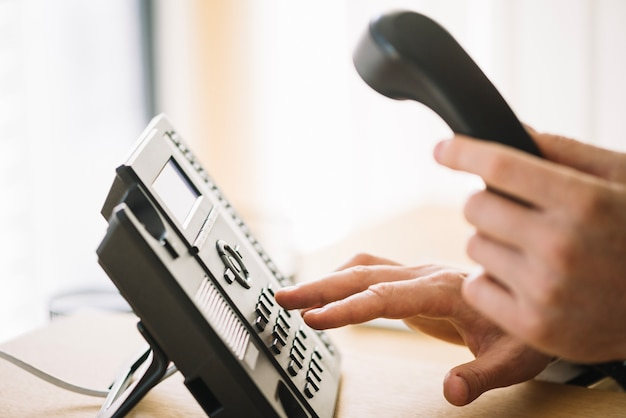 Man dialing number on phone Free Photo
