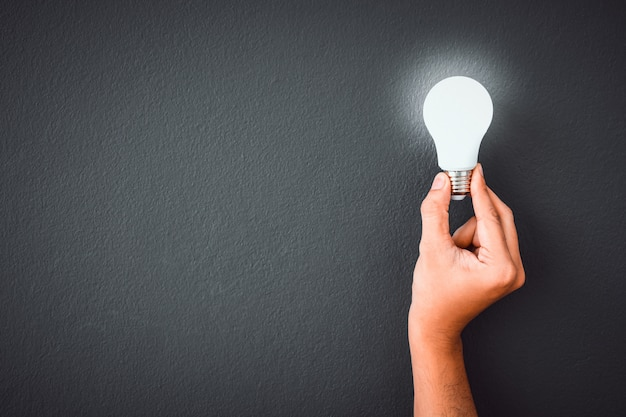 Premium Photo Man S Hand Holding Led Light Bulb Over Black Color Wall Background