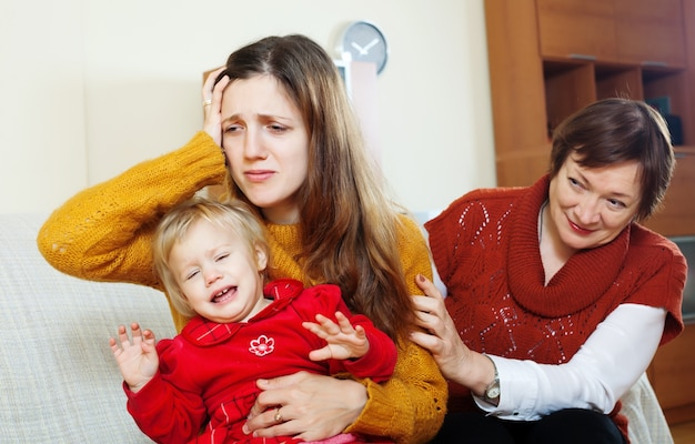 Mature woman comforting adult daughter with baby Free Photo