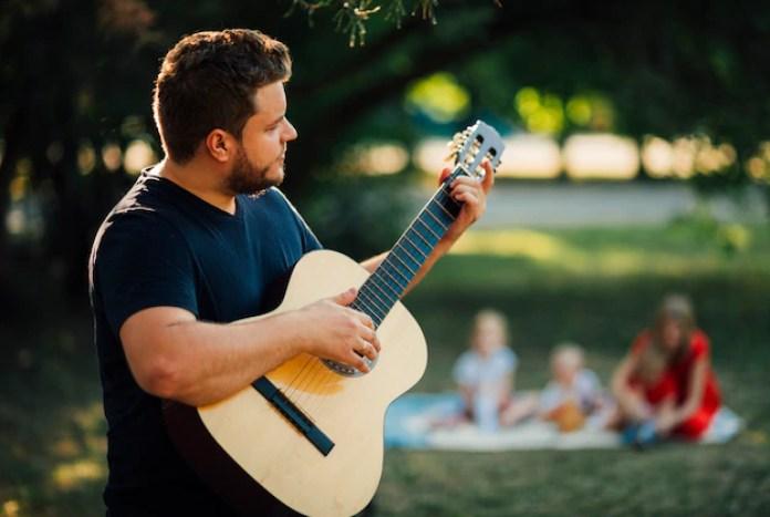 Medium shot sideways father playing guitar Free Photo
