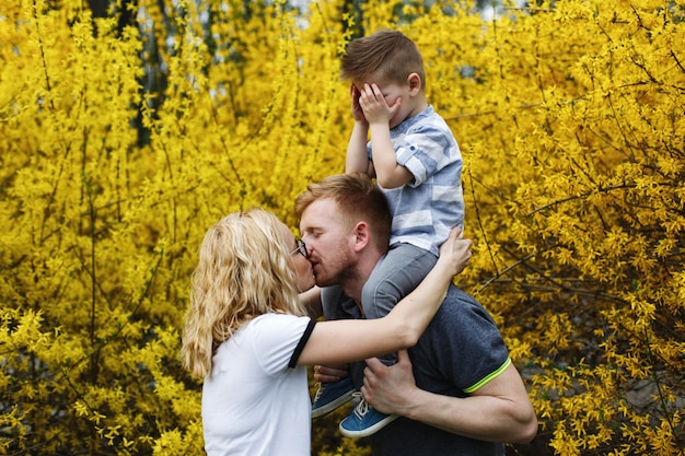 Mom and dad kiss while their little son closes his eyes Free Photo