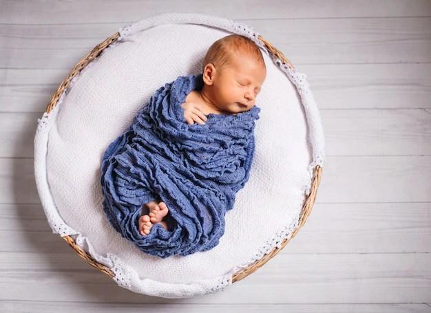 Menino bebê recém-nascido enrolado dormindo