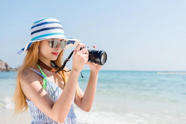 背景に地平線とビーチでカメラと一緒に撮影休暇のアジア人の女性。 無料写真