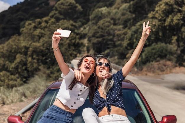 自己肖像画を撮って車のフードに座っている女性の友達 無料写真