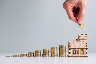 A person's hand investing money in buying house Free Photo