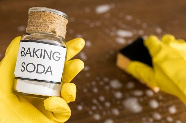Person wearing protection gloves using baking soda Premium Photo