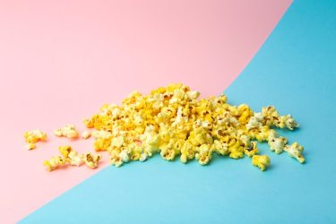 Premium Photo Popcorn on a colored background minimal food concept entertainment film and video content aesthetics 80s and 90s concept