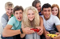 Portrait of teenagers playing video games in the living ...