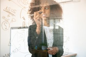 Pretty young businesswomen writing on glass board. confident experienced african american female manager holding marker and smiling in office room. strategy, business and management concept Free Photo