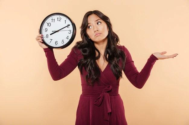 彼女が遅れているか桃の背景を気にしないように8ジェスチャー後の時間を示す時計を保持している長い巻き毛を持つ困惑したブルネットの女性   無料の写真