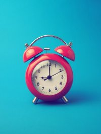 Red alarm clock on blue background Photo | Free Download