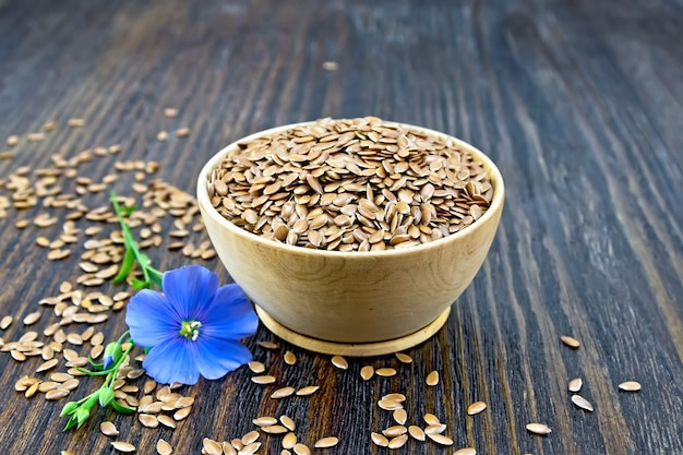 Seeds of linen brown in a bowl, blue flax flower on a wooden plank background Premium Photo
