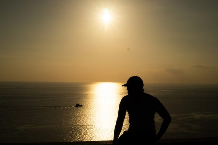 Premium Photo | Silhouette photo of man with sunset and sea view.