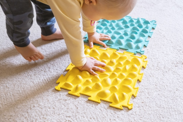 Small baby play with the ribbed rug. Free Photo