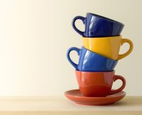 Stack of colorful coffee cups on table Photo | Free Download
