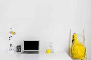Stylish workplace in white and yellow colors with backpack and laptop Free Photo