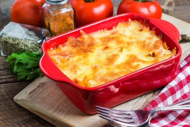Tasty lasagna in a red container Free Photo