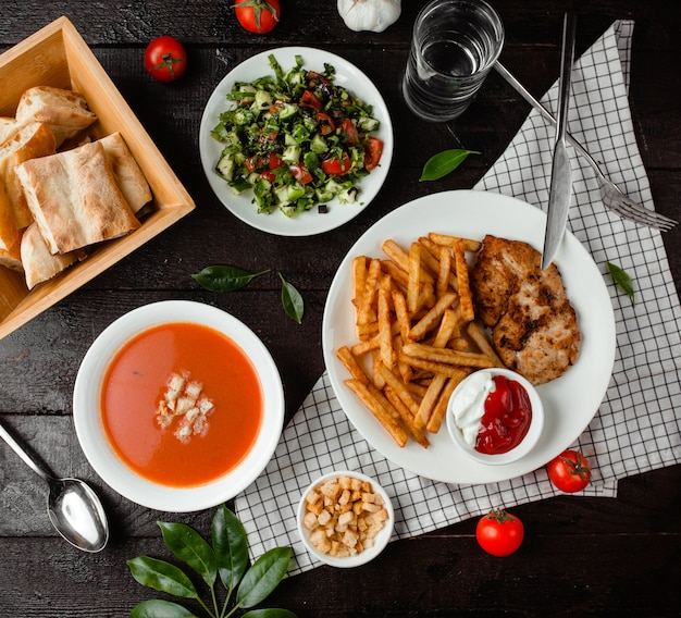 Free Photo | Tomato soup. vegetable salad and chicken with french fries